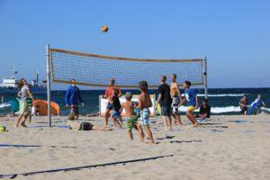Ausgelassenes Beachvolleyballspiel am Sport Aktiv Strand im Sommer.